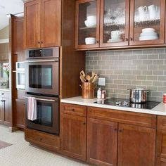 White countertop, colored subway tile and wood cabinets