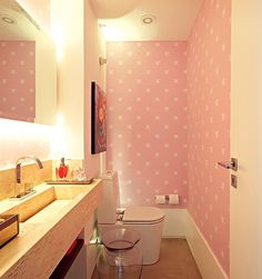 Em um apartamento de cores intensas, a arquiteta Carol Lovisaro, da Lovisaro Arquitetura e Design, criou um lavabo todo em cor-de-rosa com um papel de parede. A iluminação de xenon, embutida atrás do espelho, tem uma luz mais suave e evita que a cor se torne cansativa