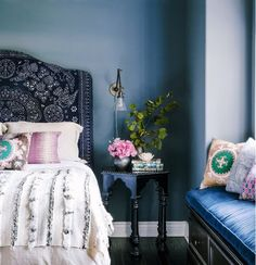 In this eclectic bedroom, a deep indigo headboard is freshened up by a cool and sexy blue wall color. A variety of blue tones in the space, from the window seat upholstery to the wall color, creates visual depth, while high-gloss black accents add textural interest.