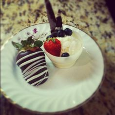 white chocolate cup, vanilla ice cream, garnished with strawberries and blueberries.