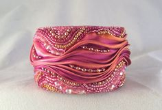 One of a kind bead embroidered shibori silk cuff. Hand stitched one to two beads at a time. Each piece is unique and created with no plan in mind. Beading as I go and letting the beads talk to me. Cuff measures 6 inches in length and 1 inch 3/4 in width. Inside is a metal cuff that is adjustable to most wrist sizes. Cuffs are backed with ultra suede for comfort.