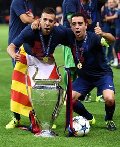 Jordi Alba (L) and Xavi Hernandez of Barcelona celebrate with the trophy after the UEFA Champions League Final between Juventus and FC Barcelona at Olympiastadion on June 6, 2015 in Berlin, Germany.