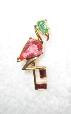 "One of almost 40 pins we bought at the Joan Rivers' estate auction--these were her favorite pins that she actually wore, from her personal jewelry box! A wonderful gift or treat yourself to a piece of history from a true queen of comedy and wonderful designer. The petite flamingo, Faberge inspired. Gold tone and pink, green and red crystals. Pictures shown with and without flash. Approximate measurements: 1 1/8"" x 1/2"".  Condition: superb!"