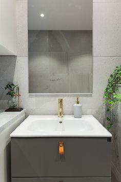 Badrum med detaljer i mässing och grå badrumsmöbler | Ballingslöv