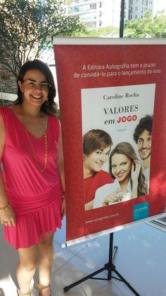 Escritora Caroline Rocha ao lado do banner do lançamento