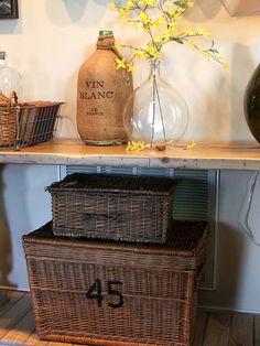 Stenciled wicker trunk, demijohn, and wire baskets