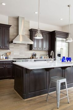 Kitchen remodel; Island; stool; espresso cabinetry; sink; lighting; pendant; vein cut travertine; Caesarstone | Interior Designer: Carla Aston / Photo: Tori Aston
