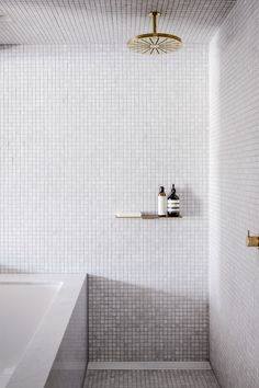 The wet room is lined with Artedomus carrara marble mosaic tiles. The architects also incorporated brass accents including a Vola showerhead and shelf by Rogerseller.
