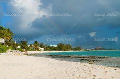 Gathering rain clouds over a tropical beach on the Caribbean island of Grand Cayman produce a very short-lived rainbow #Caribbean #Cayman