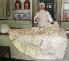 A tailor showing off a beautiful gown at Colonial Williamsburg.