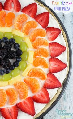 Rainbow Fruit Pizza has a sugar cookie crust covered with a cream cheese spread and topped with fruit (strawberries, clementines, pineapple, grapes, blueberries and blackberries). This beautiful dessert is perfect for picnics and barbecues - Rainbow Fruit Pizza Recipe on Gator Mommy Reviews