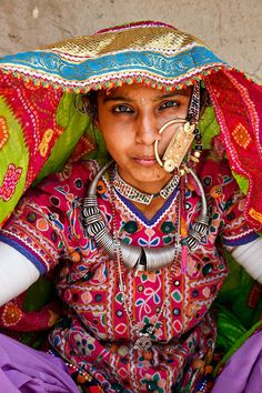 India | Portrait of a married Harijan woman. Gujarat. Harijan people originally came from Marwar in Rajasthan and they are experts in weaving wool and cotton, the Harijan women wear brightly coloured embroidered clothing and once married wear a large golden ring through their nose | © Kimberley Coole