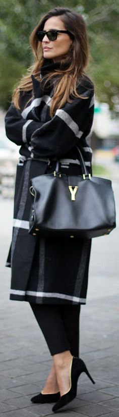 A fashion victim who's wearing a black and white checked coat, a leather bag and a high-heels.