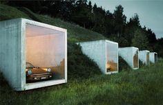 Garage de luxe par Peter Kunz  Je vous présente ce magnifique parking inspiré de l'univers de James Bond, situé à Herdern en Suisse allemande, nous devons cette création rétro futuriste à l'architecte Peter Kunz.  L'alignement des cubes de béton évoque une installation contemporaine dont l'effet sculptural s'intègre à la nature environnante.