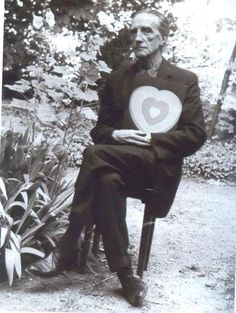 Marcel Duchamp holding one of his Fluttering Hearts (Coeurs volants)