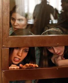 Nadezhda Tolokonnikova, left, Yekaterina Samutsevich, top, and Maria Alyokhina, right, members of female punk band 'Pussy Riot,' look out from the defendant's cell in a courtroom in Moscow on July 30, 2012. Three young women who staged an irreverent punk-rock protest against Vladimir Putin on the altar of Russia's main cathedral go on trial on Monday in a case seen as a test of the president's tolerance of dissent. (Reuters/Maxim Shemetov).