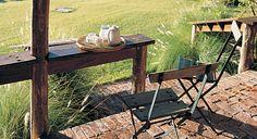 Una galería con vista al campo, con sillas plegables de hierro y asiento de madera