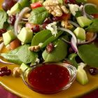 Harvest Salad-     1/2 cup chopped walnuts      1 bunch spinach, rinsed and torn into bite-size pieces      1/2 cup dried cranberries      1/2 cup crumbled blue cheese      2 tomatoes, chopped      1 avocado - peeled, pitted and diced      1/2 red onion, thinly sliced             2 tablespoons red raspberry jam (with seeds)      2 tablespoons red wine vinegar      1/3 cup walnut oil      freshly ground black pepper to taste      salt to taste.