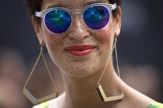 A fashionista wearing sunglasses smiles as she walks around Lincoln Center during New York Fashion Week in the Manhattan borough of New York September 6, 2014. REUTERS/Carlo Allegri
