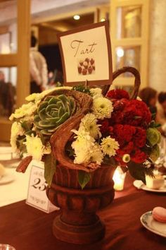 Earthen/terracotta pots with flower cacti, twigs also holds Table Marker.  Florist:  Spruce Floral Designs