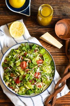 cup slivered almonds 8 strips bacon 1 romaine lettuce head 2 stalks curly kale, stems removed 1 pint cherry tomatoes, halved 1 cup shredded mozzarella cheese 1/2 cup shredded Parmesan cheese 1 cup croutons, coarsely chopped Dressing 1/4 cup lemon juice 2-3 big garlic cloves, minced 3/4 cup olive oil Salt and Pepper, to taste
