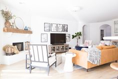 Tulsa Remodel Reveal Modern White Farmhouse white brick fireplace wood beam mantle modern leather couch fiddleleaf fig tree tv gallery wall-1