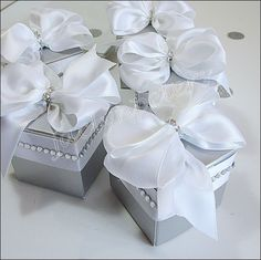 Elegant handmade silver favor boxes are accented with a luxury white double satin ribbon and rhinestone trim. Your table decor will sparkle while thanking guests for sharing your celebration Fabulous                                                                                                                                                                                  More