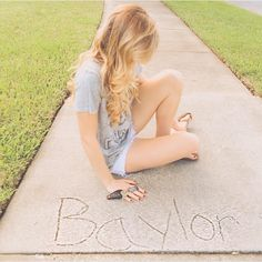 """While pushing a stroller nannying, Amber asked God for clarity and a clear sign as to where he saw her in the coming semester. She looked down as the stroller passed over a large bump. To her surprise, written in the concrete was the word """"Baylor."""" She drove back to that neighborhood and sat down next to that beautiful reminder and captured this moment. Sometimes, God responds in ways that are clear as concrete."""