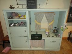 Repurposed entertainment center with a vintage twist. Check out the Avon decanter faucet !!