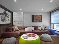 A chunky sectional anchors the family room and together with crocheted ottomans, provides ample seating. Toys are stashed in the custom millwork as well as in the base of the round coffee table #ExtraStorage #RevampInteriorDesign #WildlyElegantDesign