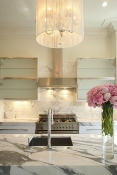 Love this kitchen including the pale aqua glass door cabinets, and the pink flowers.  Marble waterfall counter