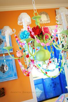 Painted chandelier made of glass and plastic beads & baubles, buttons, flowers, rhinestone jewelry, upside down tea cups, birds, etc. How fabulous for an over the top tea party for your little girl!