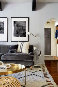 Emily Henderson designed living room | dark velvet grey sofa + round brass coffee table + skinny side table + white ourain rug