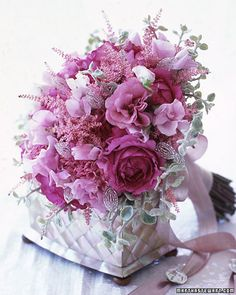 This bouquet combines sweet peas, roses, and feathery astilbe with helichrysum and beaded leaves. Virtually invisible until they catch the light, individual pink sequins affixed to wire stems are interspersed among the blooms. On the handle, mother-of-pearl buttons dangle from metallic-pink ribbon.