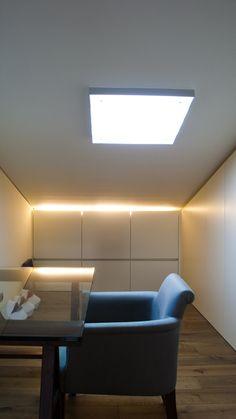 Wandkasten uitgevoerd in gelakte MDF, onder schuin aflopend plafond.