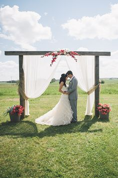 Keep your wedding ceremony altar subtle but elegant. A wooden structure and potted flowers take a cue from the outdoors, with gauzy drapes completing the look.