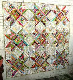 Very pretty string quilt!  Each block would be just as easy to  make as a typical string block-- a certain number in saturated colors and another number in pastels/neutrals-- though putting it together would require planning.