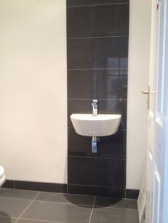 Simple and Stylish. Cloakroom in Lounge Tiles Grey, floor tiled with 100mm upstand and 1 row floor to ceiling behind basin.