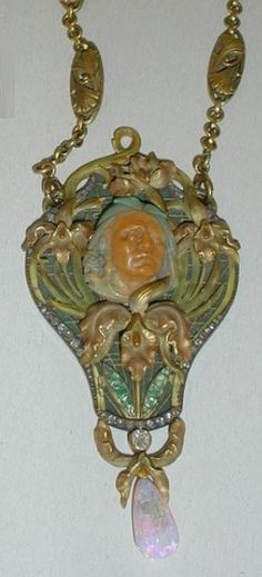 An Art Nouveau gold, opal and paste pendant necklace, by Georges Henry, French, circa 1900. Depicting a face of a native American surrounded by orchids. #GeorgesHenry #ArtNouveau #pendant