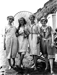 Four young Edwardian women in bathing costumes posing for the camera at the beac., Beach Outfits, Four young Edwardian women in bathing costumes posing for the camera at the beach, circa