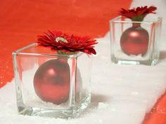 Neem een glazen blokvaas, een kerstbal en een rode gerbera (of andere kleur/bloem). Klaar. Cute.