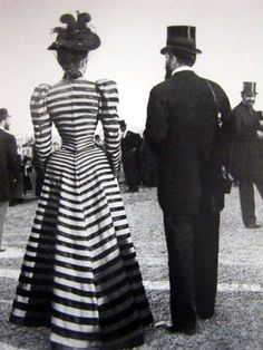 1890 striped dress with leg-of-mutton sleeves. These sleeve begin in a large puff at the shoulder and taper to become very right at the wrist.