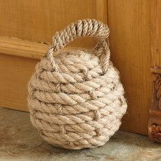 Nautical Knot Rope Doorstop - Looking for an interesting nautical-themed decorating element? Consider this handy rope doorstop. Made of heavy duty, knotted hemp rope surrounding a weighted cement base, it will keep your heaviest doors open and stay in place no matter where you put it.