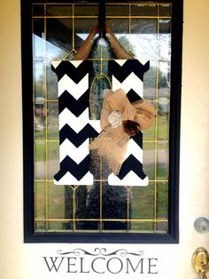 Monogram door with letter of last name with bow instead of a traditional wreath. Might try this!