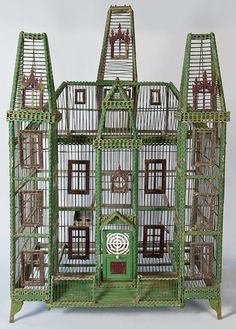 Large Painted Tramp Art Bird Cage     Green painted tramp art style bird cage in the form of a three story Victorian house with porch, railing, 17 windows with a hinged door and two perches.  American, c.1900