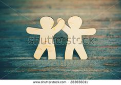 Wooden little men holding hands on wooden boards background. Symbol of…