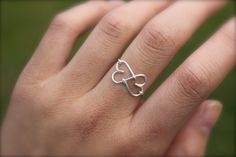 As a symbol of eternal love, this double heart ring features two interlocking hearts that resemble an infinity symbol. It is made out of non-tarnish silver or gold wire; it is also available in sterli