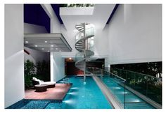 House at Jalan Angin Laut, showing the transparent glass bridge over the swimming pool. The spiral staircase leads to the guest bedroom and a gym on the 3rd storey. The glass bridge leads from the entrance to the living room.