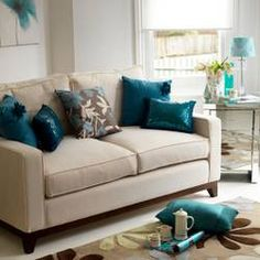 White couch, teal pillows