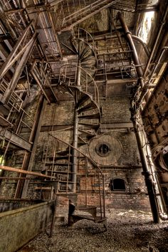 """Inside the abandoned power house at the site of the old Mohasco carpet mill in Amsterdam, N.Y.  The place is massive, and the coal-fired boilers are enormous. I wanted to get an overhead view of it all from the catwalks, but the only way up is this staircase, which has a major crack in the center post and is a bit wobbly. The catwalks themselves have had rain dripping on them for decades, so who knows how weak they are.  More photos and a bit of history on the factory in the """"Carpet City""""…"""